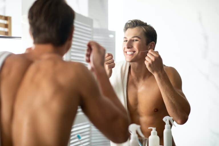 Handsome young man using dental floss in bathroom
