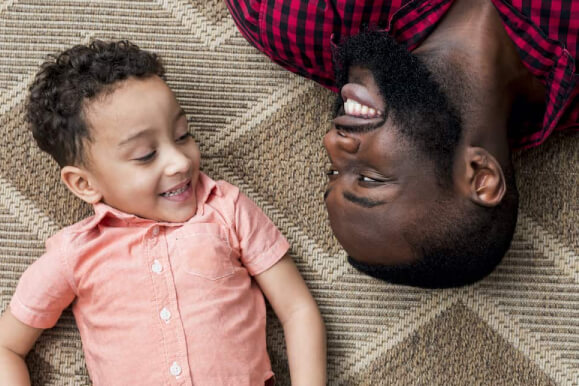 a smiling kid and a black man lying opposite at each other on a woven brown mat