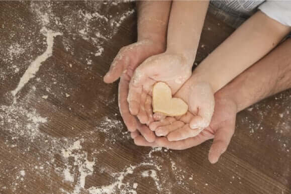 a person's hand supporting a kid's hand that's holding a dough heart